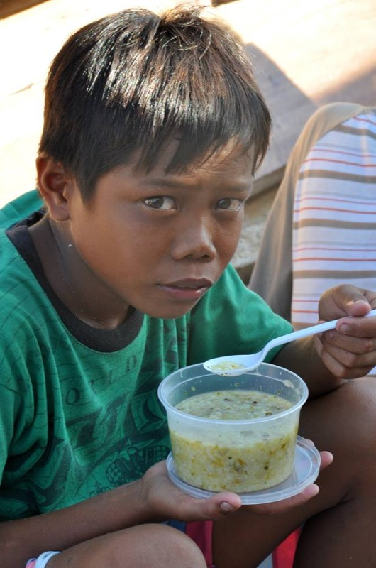 Boy eating a meal. Photo by Malapascua Relief Project.